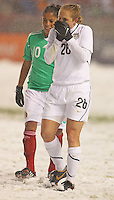 USA's Rachel Buehler (R) blows on her hands to keep warm during a match with Mexico's at Rio Tinto Stadium March 31, 2010 in Salt Lake City, Utah. The USA women won the match over Mexico 1-0.