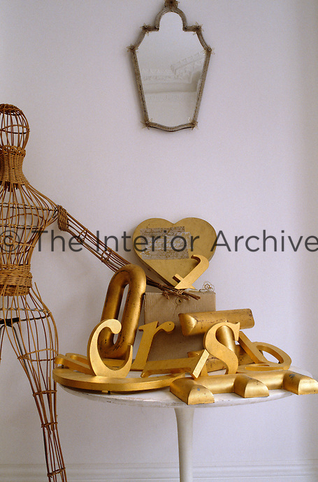 A wicker mannequin stands beside a pile of gold letters on a small round table