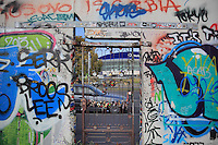 A gate in a hole in the Berlin Wall where people have attached padlocks, and graffiti covering this side of the Wall, part of the East Side Gallery, a 1.3km long section of the Wall on Muhlenstrasse painted in 1990 on its Eastern side by 105 artists from around the world, Berlin, Germany. Picture by Manuel Cohen