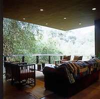 The living room gives one the sense of being in a tree house as it is open to the tree tops