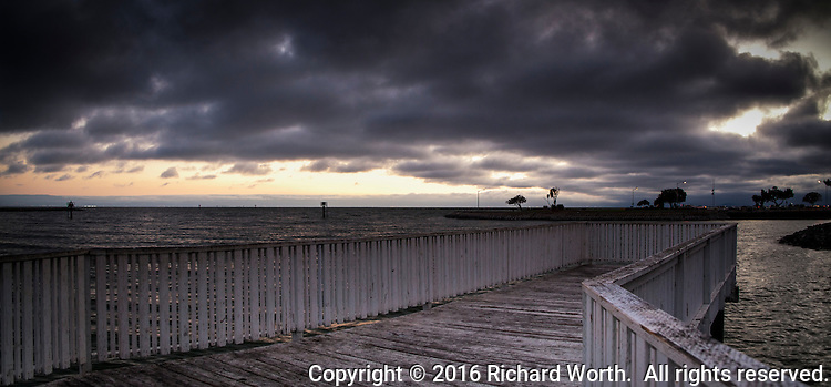 Dramatic clouds, enhanced with software, compensate for the lack of color in the sky at sunset seen from a fishing pier on San Francisco Bay.