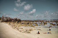 Young kids relax in the Nauruan seashore...Nauru, officially the Republic of Nauru is an island nation in Micronesia in the South Pacific.  Nauru was declared independent in 1968 and it is the world's smallest independent republic, covering just 21square kilometers..Nauru is a phosphate rock island and its economy depends almost entirely on the phosphate deposits that originate from the droppings of sea birds. Following its exploitation it briefly boasted the highest per-capita income enjoyed by any sovereign state in the world during the late 1960s and early 1970s..In the 1990s, when the phosphate reserves were partly exhausted the government resorted to unusual measures. Nauru briefly became a tax haven and illegal money laundering centre. From 2001 to 2008, it accepted aid from the Australian government in exchange for housing a Nauru detention centre, with refugees from various countries including Afghanistan and Iraq..Most necessities are imported on the island..Nauru has parliamentary system of government. It had 17 changes of administration between 1989 and 2003. In December 2007, former weight lifting medallist Marcus Stephen became the President.