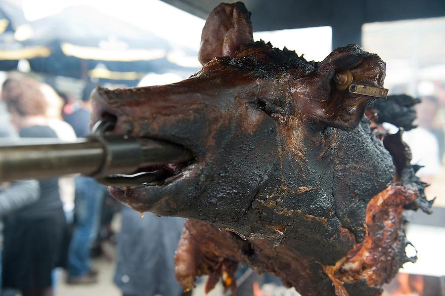 Nederland, Ermelo, 7 aug 2010.Varken aan het spit op een festival. Na uren grillen boven een vuurtje is dit varken klaar op gegeten te worden. Het lijkt zwartverbrand, maar dat is alleen de huid...Foto Michiel Wijnbergh..Pig on a spit at a festival. After hours of grilling over a fire this pig is ready to be eaten. It seems burned black, but that's only the skin... .