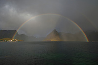 Rainbow shines in Reinefjord over Olstind mountain peak, Toppøy, Lofoten Islands, Norway