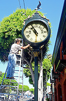 Richard Golawski paints the New Orleans Building Clock on Main Street on Tuesday, Aug 14, 2012.