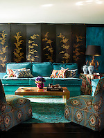 In a glamorous sitting room, the slipper chairs are upholstered in a cotton velvet by Lewis & Wood and the sofa are by Nicholas Haslam Ltd., The ikat cushions are from Istanbul. A 19th century Korean screen with a leaf motif stands behind the sofa. The table covering is in a linen by Jim Thompson, and the rug is by the Rug Company.