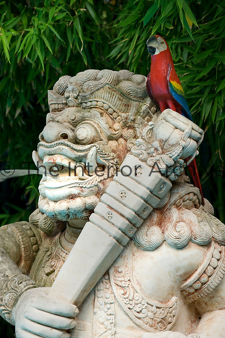A hand-painted wooden parrot sits on the shoulder of a stone statue of a Hindu god that is also a water feature