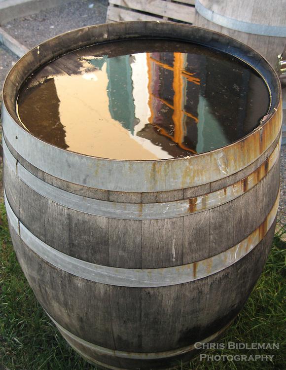 Water reflection in wine barrel of building window