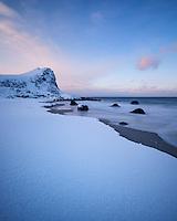 Sea meets snow at Myrland beach in Winter, Flakstadøy, Lofoten Islands, Norway