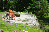 Patio Deck made from existing stone boulders with wooden Adirondack chairs furniture and container wine barrel planter garden, using the landscape to integrate natural landscape in the backyard landscaping