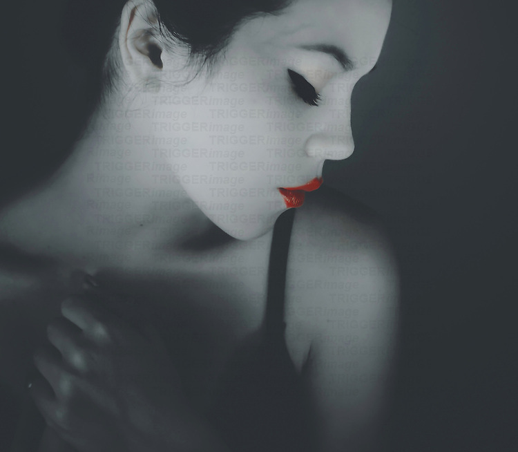 Proflie of young woman with eyes closed and red lips looking to side