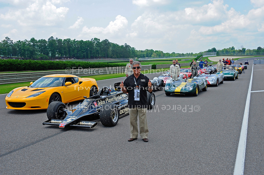 """Honored Guest"" Mario Andretti poses with a gridfull of Lotus cars, their drivers and the #5 Lotus 79 F1 car that he won the 1978 World Championship with."