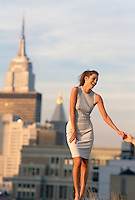 Woman enjoying standing on a rooftop while holding a man's hand overlooking the Empire State Buidling in New York City