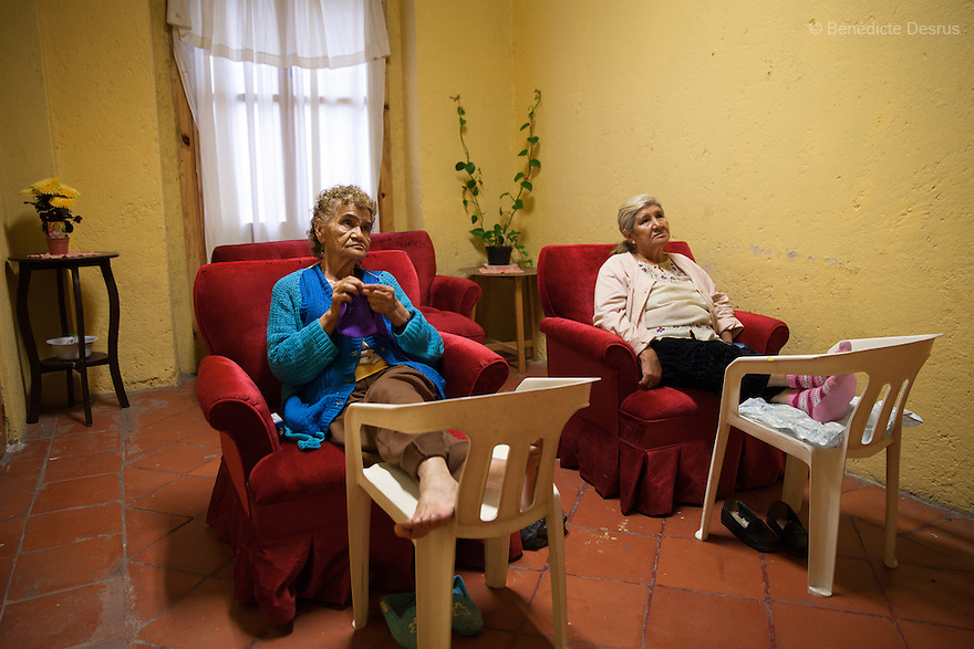 Victoria and Gloria, both residents of Casa Xochiquetzal, watch television at the shelter in Mexico City, Mexico on June 14, 2013. Casa Xochiquetzal is a shelter for elderly sex workers in Mexico City. It gives the women refuge, food, health services, a space to learn about their human rights and courses to help them rediscover their self-confidence and deal with traumatic aspects of their lives. Casa Xochiquetzal provides a space to age with dignity for a group of vulnerable women who are often invisible to society at large. It is the only such shelter existing in Latin America. Photo by Bénédicte Desrus
