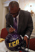 ECU coach Ruffin McNeil signs a helmet after the 9th annual Bill Dooley Pigskin Preview on Thursday, July 21, 2011. Photo by Al Drago.