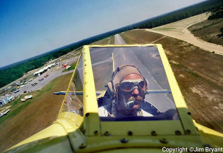 "Kurt Miles, known as the ""Flying Mayor of Milton"", pilots his vintage biplane over the runways of Northwest Florida during a fly in on Sunday, June 9, 2002. (Jim Bryant photo)"