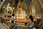 St. Patrick's Cathedral, 5th Avenue, New York City, two girls lighting votive candles at Our Lady of Guadalupe Shrine, at Fifth Avenue, Manhattan, NYC, New York, USA, on June 27, 2011