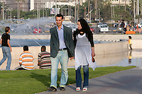 Tripoli, Libya, North Africa - Dress Styles in Contemporary Libya.  Couple Walking in a Public Park near the Green Square, in downtown Tripoli.  Women typically cover their heads with a scarf, but may wear jeans, levis, or a traditional abaya, a loose-fitting ankle-length garment.  This woman has red-painted toenails.  Men wear European or western-style attire.