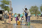 A boy drinks water from a newly drilled well in an internally displaced persons camp in Aweng, South Sudan. Families started arriving here shortly after fighting broke out in December 2013, and new families continued to arrive in March 2014 as fighting continued. The ACT Alliance is providing the displaced families and the host communities affected by their presence with a variety of support, including the drilling of this and other new wells.
