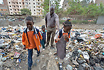 Abdel Karim, a refugee from the Darfur region of Sudan, walks his children to school in the morning through the trash-strewn streets of Cairo, Egypt. Karim and his wife have both taken adult education classes provided by St. Andrew's Refugee Services, which is supported by Church World Service. His children, from left, are Ziad, 9; Ahmed, 4; and Dana, 7.