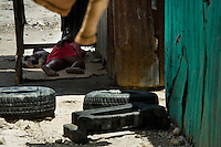 A Haitian mother sleeps with her kid on a cardboard in the slum of Cité Soleil, Port-au-Prince, Haiti, 16 July 2008. Cité Soleil is considered one of the worst slums in the Americas, most of its 300.000 residents live in extreme poverty. Children and single mothers predominate in the population. Social and living conditions in the slum are a human tragedy. There is no running water, no sewers and no electricity. Public services virtually do not exist - there are no stores, no hospitals or schools, no urban infrastructure. In spite of this fact, a rent must be payed even in all shacks made from rusty metal sheets. Infectious diseases are widely spread as garbage disposal does not exist in Cité Soleil. Violence is common, armed gangs operate throughout the slum.