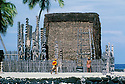 Pu'uhonua O Honaunau National Historical Park, South Kona, Island of Hawaii: man in feather cape bringing ho'okupu or offering to Hale O Keawe Heiau during annual Cultural Festival..#4415-4125
