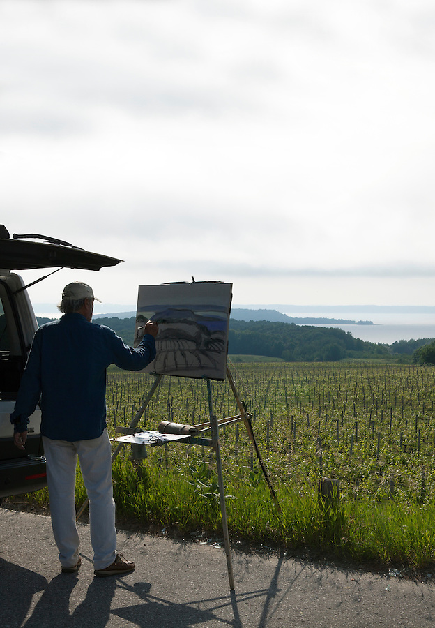 Man painting the Chateau Grand Traverse vineyards on the Old Mission Peninsula, Traverse City area, Michigan, USA