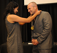 NWA Democrat-Gazette/ANDY SHUPE<br /> Pooja Naik (left), a senior at Bentonville High School who will attend Columbia University in the fall, places a medal Tuesday, May 16, 2017, around the neck of English teacher Kelly Davis during the annual Academic Signing Day in the North Lecture Hall at the school. The ceremony featured 21 of the top students in the senior class who spoke about their time at Bentonville High School and their college plans before thanking an influential teacher.