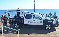 Santa Monica Harbor Patrol Officer Dan Buchanan mounts his rescue board on top of his police vehicle at the Santa Monica Pier on Tuesday, July 17, 2012.