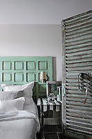 A pale green painted wooden headboard is a feature of this simple guest bedroom with a black and white striped side table