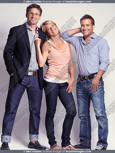 Smiling casually but with style dressed two men and a woman wearing jeans