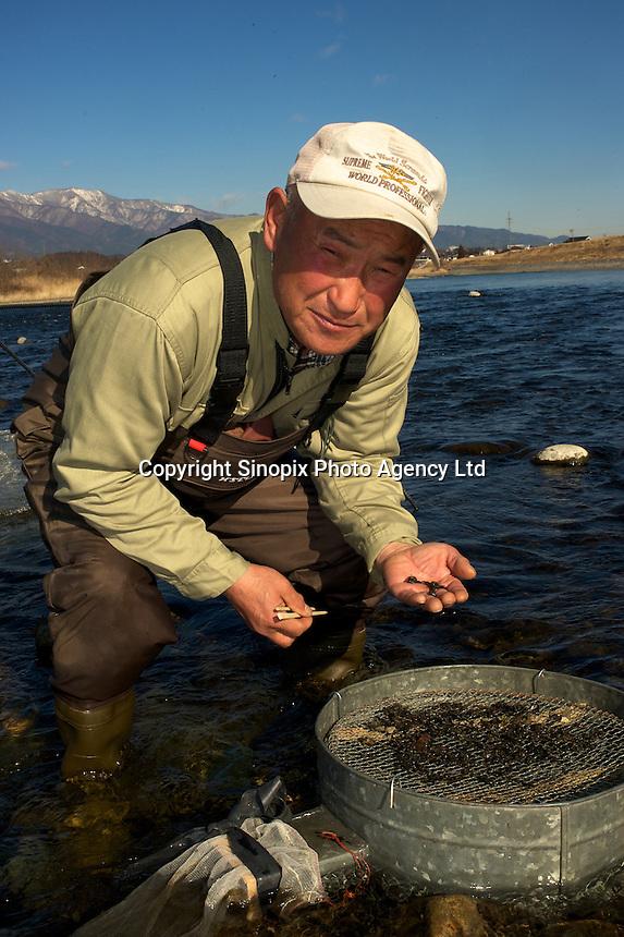 Hideo Nagatsubo, 60, stands in the Tenryu River hunting stone-fly larvae, known as  zaza-mushi, near Ina City, Nagano Prefecture, Japan.