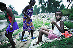 KINSHASA, DEMOCRATIC REPUBLIC OF CONGO - APRIL 29: Esther Yandakwa, age 9, waits to take a bath in a river with her friends on April 29, 2006 in Matonge district in central Kinshasa, Congo, DRC. Esther is homeless and works a prostitute together with four fourteen-year-old friends. They live outside next to a polluted river. She's been three years on the street and has run away from here mother. She has from time to time been living in a homeless shelter for children but doesn't like the rules there. She usually smokes cigarettes, marijuana, drinks whiskey and sometimes takes Valium. She charges the clients as little as US$ 1. About 15,000 children are estimated to live on the streets of Kinshasa. Congo, DRC is in ruins after forty years of mismanagement by the corrupt dictator and former president Mobuto Sese Seko. He fled the country in 1997 and a civil war started. The country is planning to hold general elections by July 2006, the first democratic elections in forty years.(Photo by Per-Anders Pettersson)