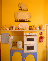 The owner of this  buttercup yellow-painted country-style kitchen is evidently obsessed with pigs!