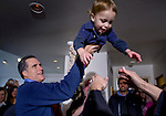 Republican presidential hopeful Mitt Romney passes his grandson Parker to Parker's mother, Mary, before greeting supporters at the McKoy residence in Clive, Iowa, on Tuesday, January 1, 2008.