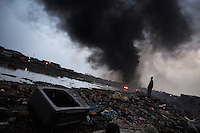 E-waste litters the ground while a huge fire burns at Agbogbloshie dump, in Accra, Ghana.