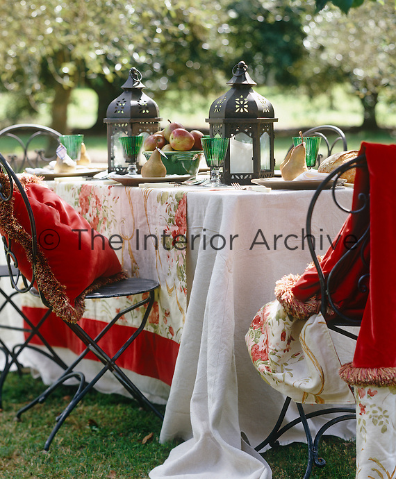 A table laid in the orchard with lanterns and fruit for an autumn inspired lunch