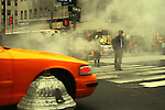 Typical New York City street scene with people, yellow cabs, and steam coming out of manholes where constant construction is going on. Manhattan, New York City.