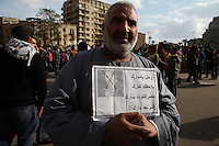 A protester at Tahrir Square holds an anti-Mubarak sign.