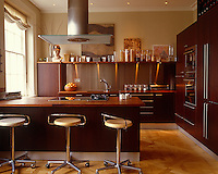 Tones of brown and beige and glowing parquet floors create a feeling of warmth and cosiness in a contemporary urban kitchen