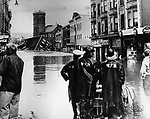 Waterbury's Brooklyn section as it looked during the height of the flood. The wrecked buildings of North Riverside Street and the former Anaconda American Brass Co. tower are in the background. The Mercer & Dunbar building stands at right.