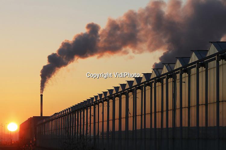 Foto: VidiPhoto<br /> <br /> BEMMEL - Ochtendgloren in het kassengebied Bergerden tussen Bemmel en Arnhem dinsdag. Kwekers moeten door de vroege winter extra stoken om hun kassen op temperatuur te houden. De nacht van maandag op dinsdag was de koudste van deze eeuw. De ontwikkeling van Bergerden tot het Westland van het Oosten is nooit van de grond gekomen. Slechts veertien kwekers zijn in het 350 ha. grote gebied neergestreken. Door de ligging, de hypermoderne infrastructuur en de gezamenlijke energievoorziening zou het de ideale locatie voor veel kleine tuinders uit de regio, maar ook voor grotere bedrijven uit Westland zijn. Kwekers en telers laten het echter nog steeds massaal afweten. Lingewaard en Nijmegen, die Bergerden samen exploiteren, zitten nog met tientallen hectares grond. Ze slikten beide al een verlies van 5 miljoen euro.