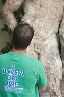 man in a tee shirt &quot;I have a big one&quot; looking at greek statue