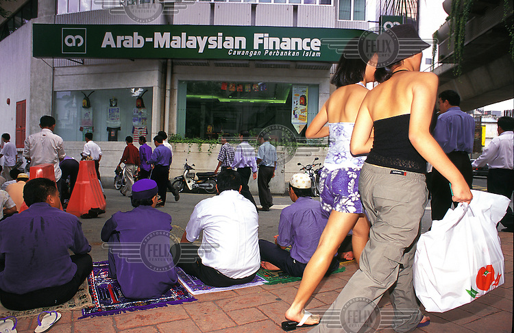 Scantily clad local girls pass by Mulsim office workers during their prayer time outside Masjid Jamie mosque in central Kuala Lumpur.  Credit: Chris Stowers.