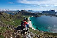 Female hiker on summit of Manen with Haukland beach in background, Vestvågøy, Lofoten Islands, Norway