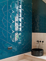 The guest washroom features Feza tiles sourced from the Turkish tile company Kale.  The washbasins are black toros solid marble, set onto Egyptian onyx countertops