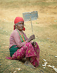 """Holding a sign that reads, """"Women join together,"""" a woman rests after a march celebrating International Women's Day on March 8, 2016, in Dhawa, a village in the Gorkha District of Nepal."""