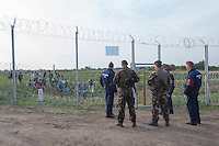 Army soldiers and police officers stand guard and send migrants away at a door on the razor wire fence on the border between Serbia and Hungary near Roszke (about 174 km South of capital city Budapest), Hungary on September 15, 2015. ATTILA VOLGYI