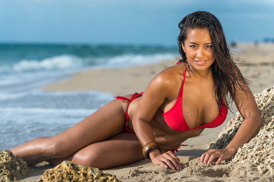 Portrait of hot female in red bikini sunbathing over the blurred beach background very happy