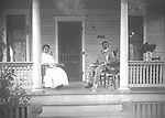 Summer Porch Scene: The house at 1821 North 29th in Lincoln was purchased by Jack and Euphemia Spicer in 1922.  He worked as a laborer, houseman, and gardener.   The dapper man may be Mr. Spicer; the young woman at left probably is his daughter Sirilda Belva Spicer (1894-1993), who graduated from University of Nebraska with a degree in education and taught for several years in Kansas City, Kansas, before entering the ministry and serving  AME churches in Nebraska in the 1940s and '50s.  She returned to education from age 62 to 76, teaching Native American children in South Dakota.<br />